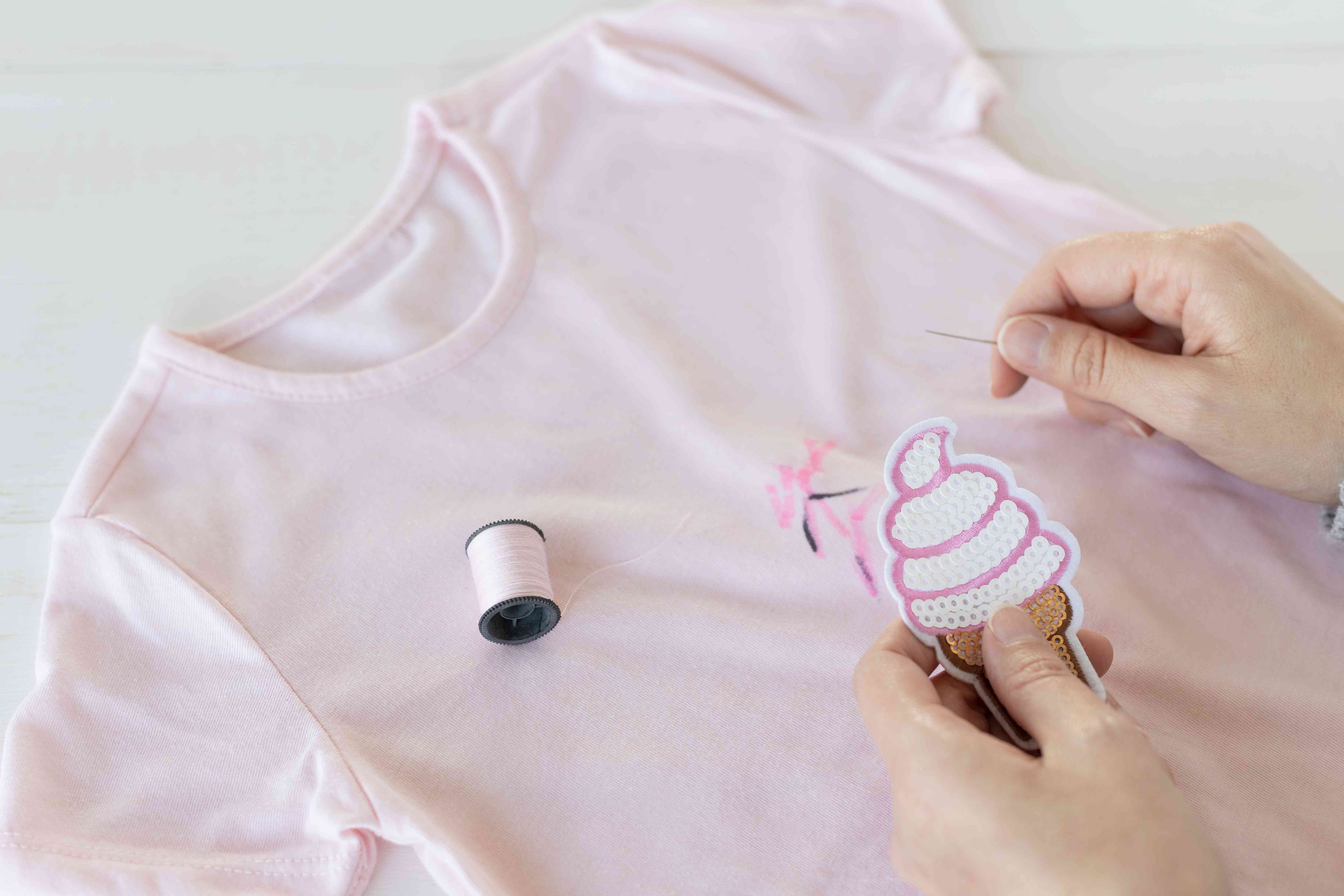 Pink shirt with stain sewing on ice cream patch with pink yarn