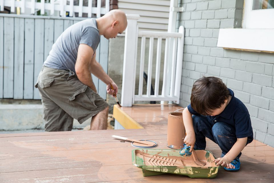 man and boy painting deck