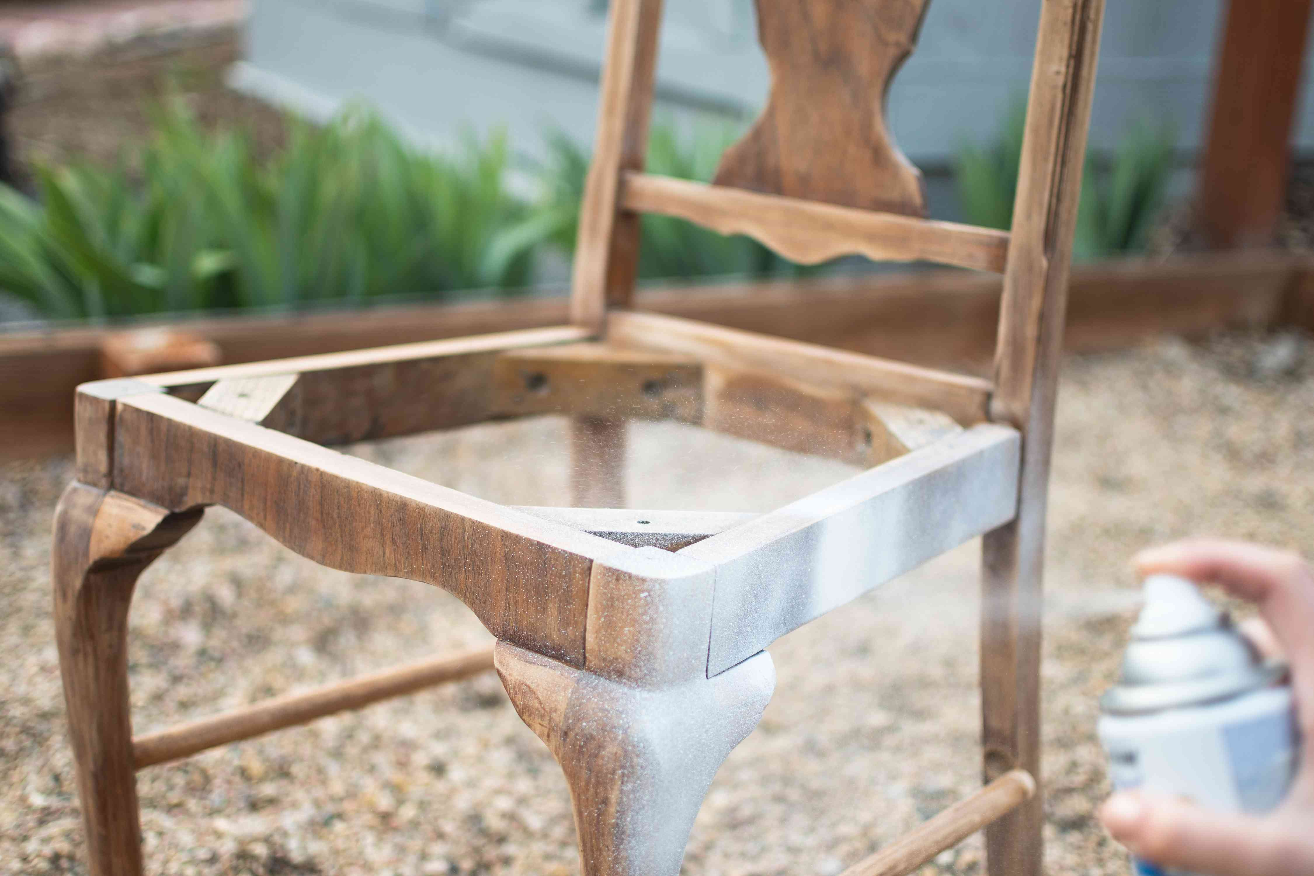 Sanded wooden chair spray painted with shite primer