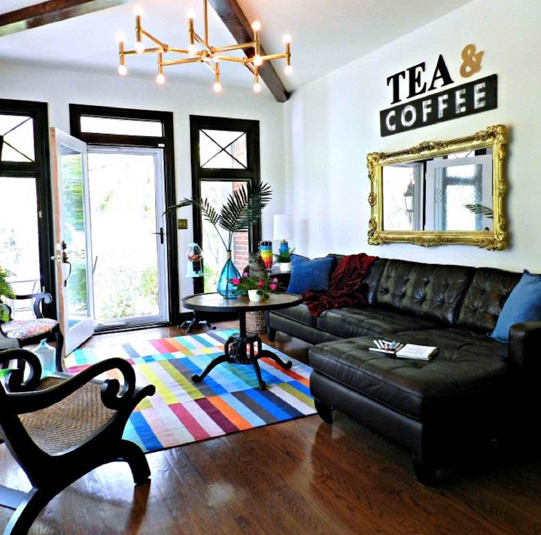 Sala de estar transformada de oficina en casa después con sección de cuero, espejo, lámpara de araña y alfombra colorida.