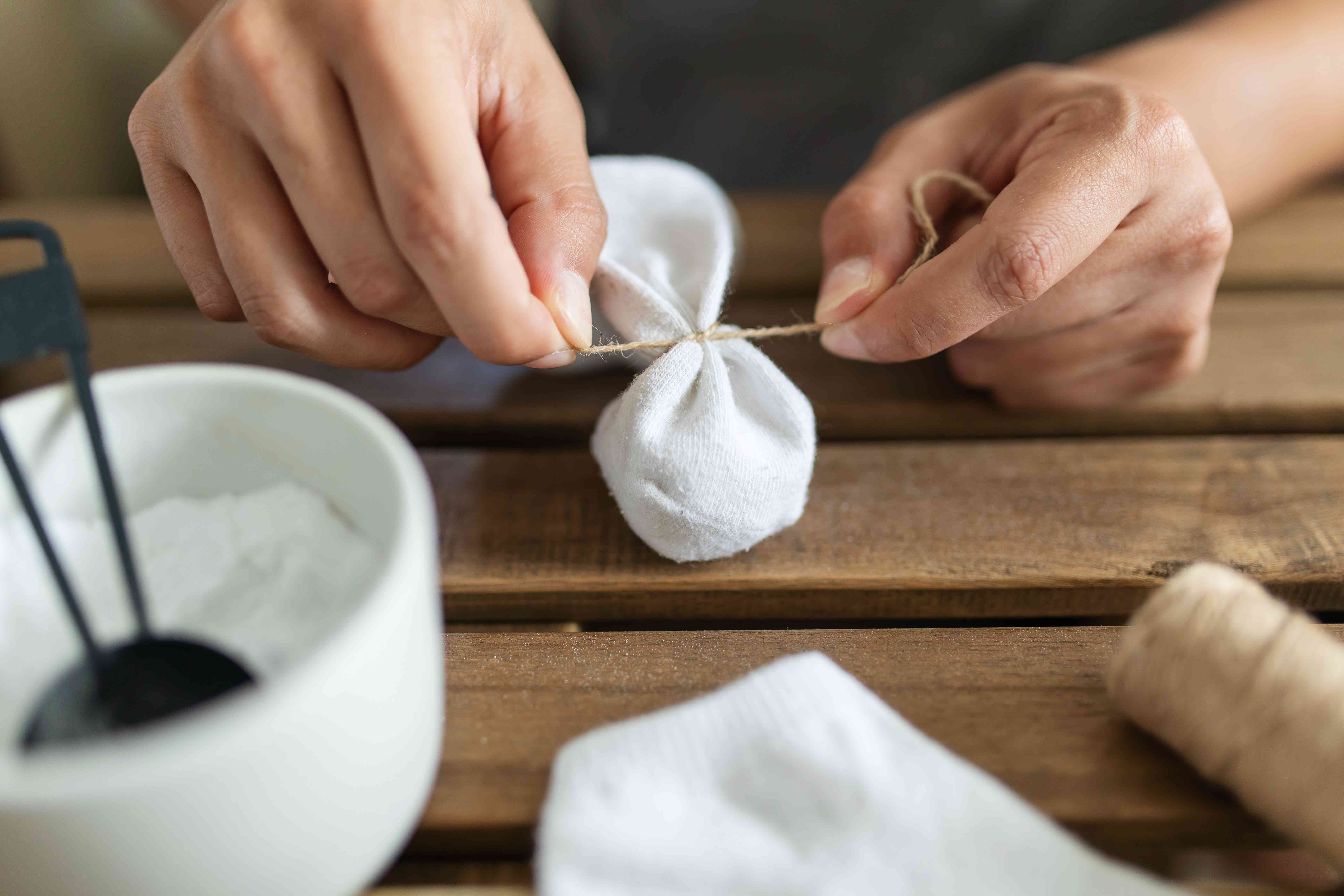 person using a string and sock to make baking soda sachets