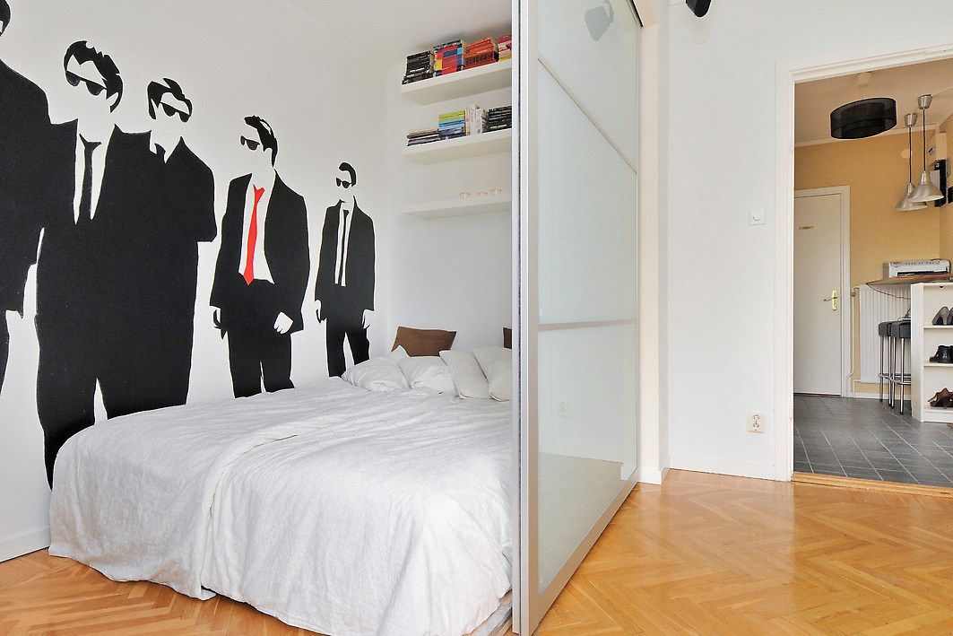 Studio apartment with room divider to separate bedroom that has male silhouettes on wall.