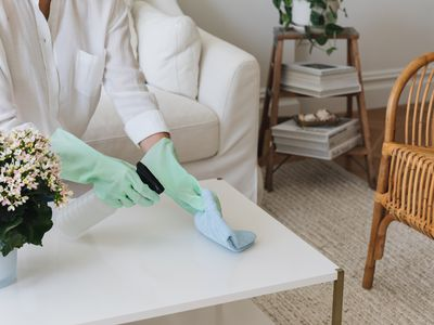 White coffee table wiped with blue towel and spray bottle for spring cleaning