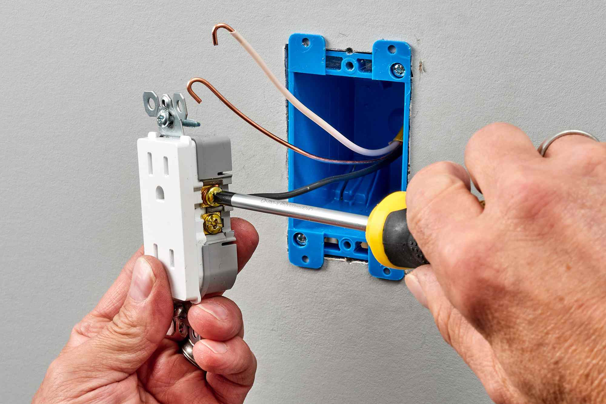 Phillips screwdriver tightening screw to secure wire