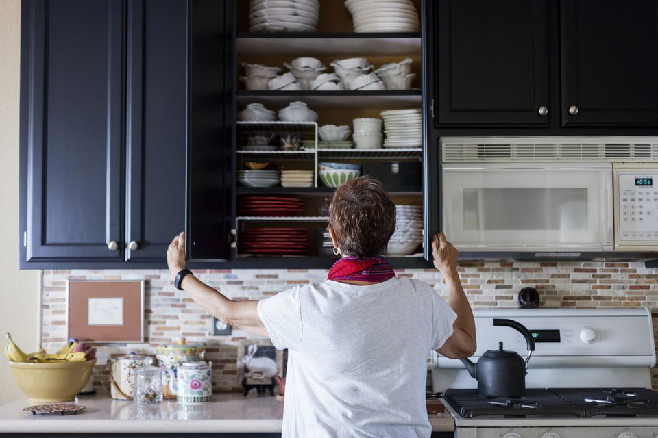 Woman checking cabinet in kitchen
