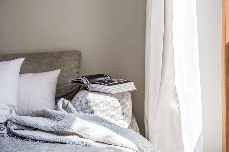 Imagen de un sofá con almohadas, mantas y un libro abierto en el borde. El sofá está al lado de una cortina blanca.