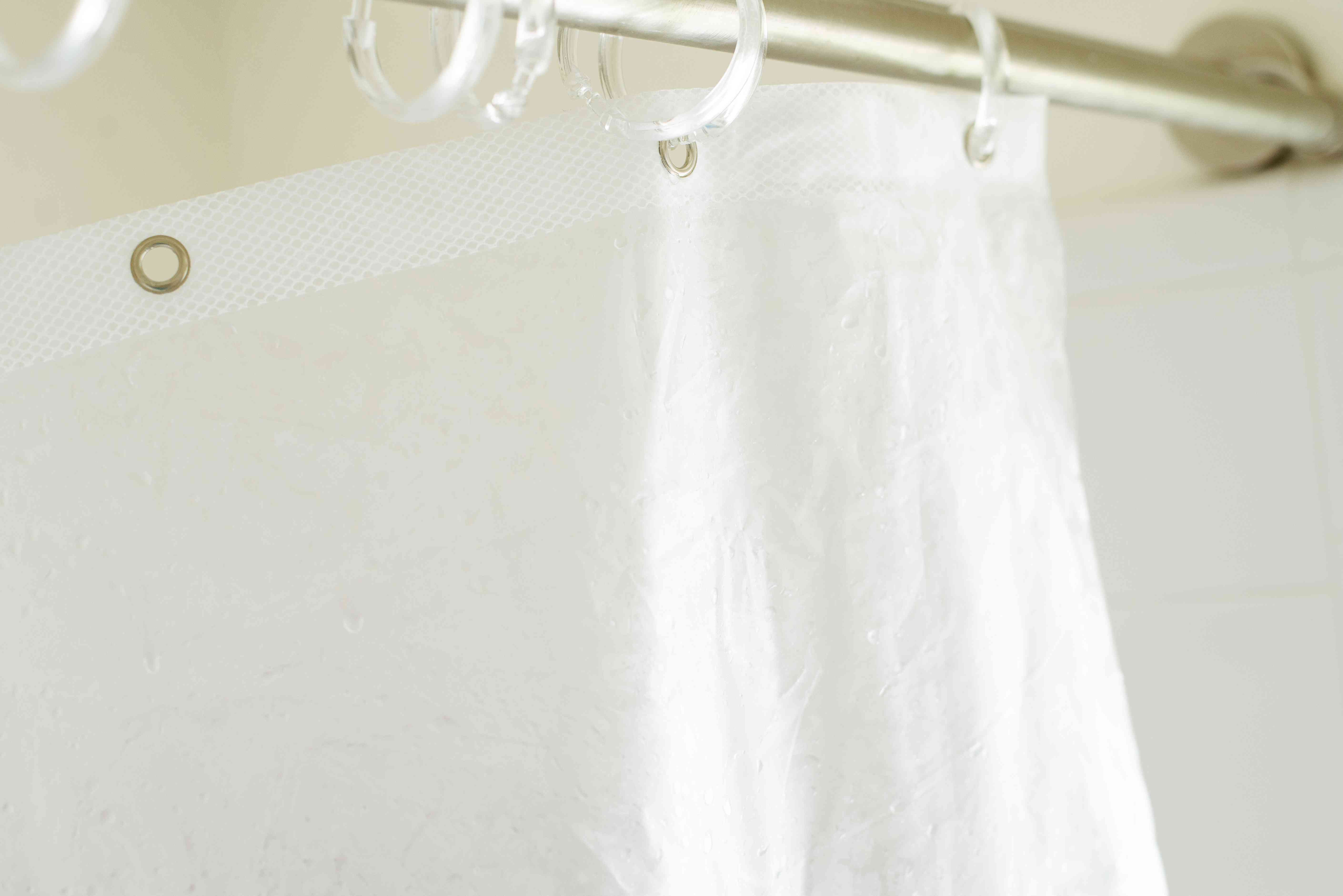 Wrinkled vinyl shower curtain held up on shower rod to air dry