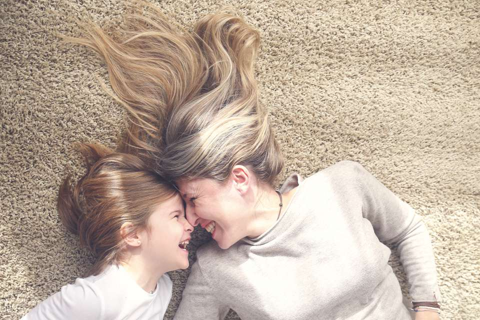 Mother and little daughter lying on carpet having fun