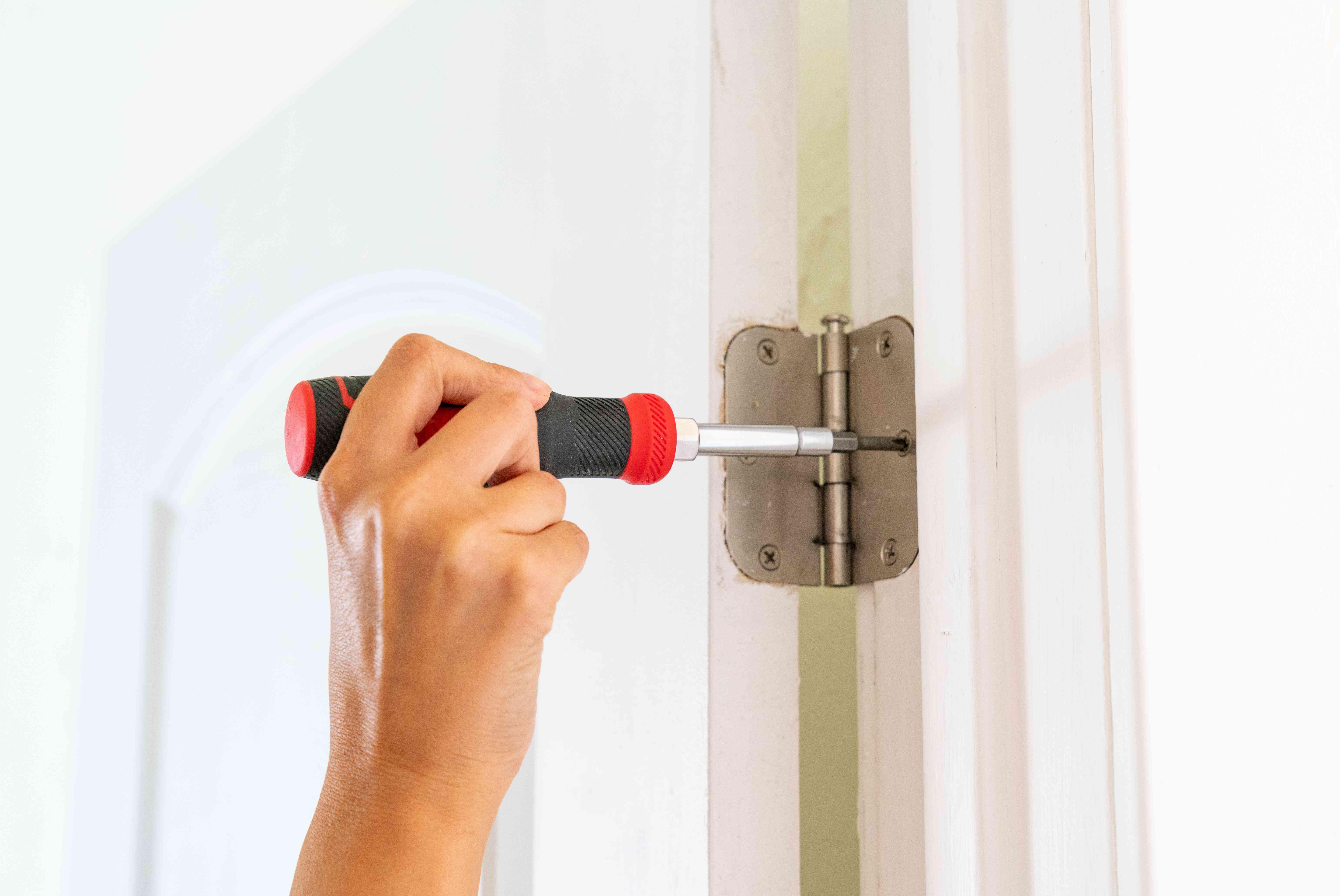 Hinge screws tightened in door frame to fix door that sticks