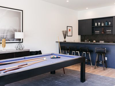 Basement room with white painted walls with purple pool table and black decor bar