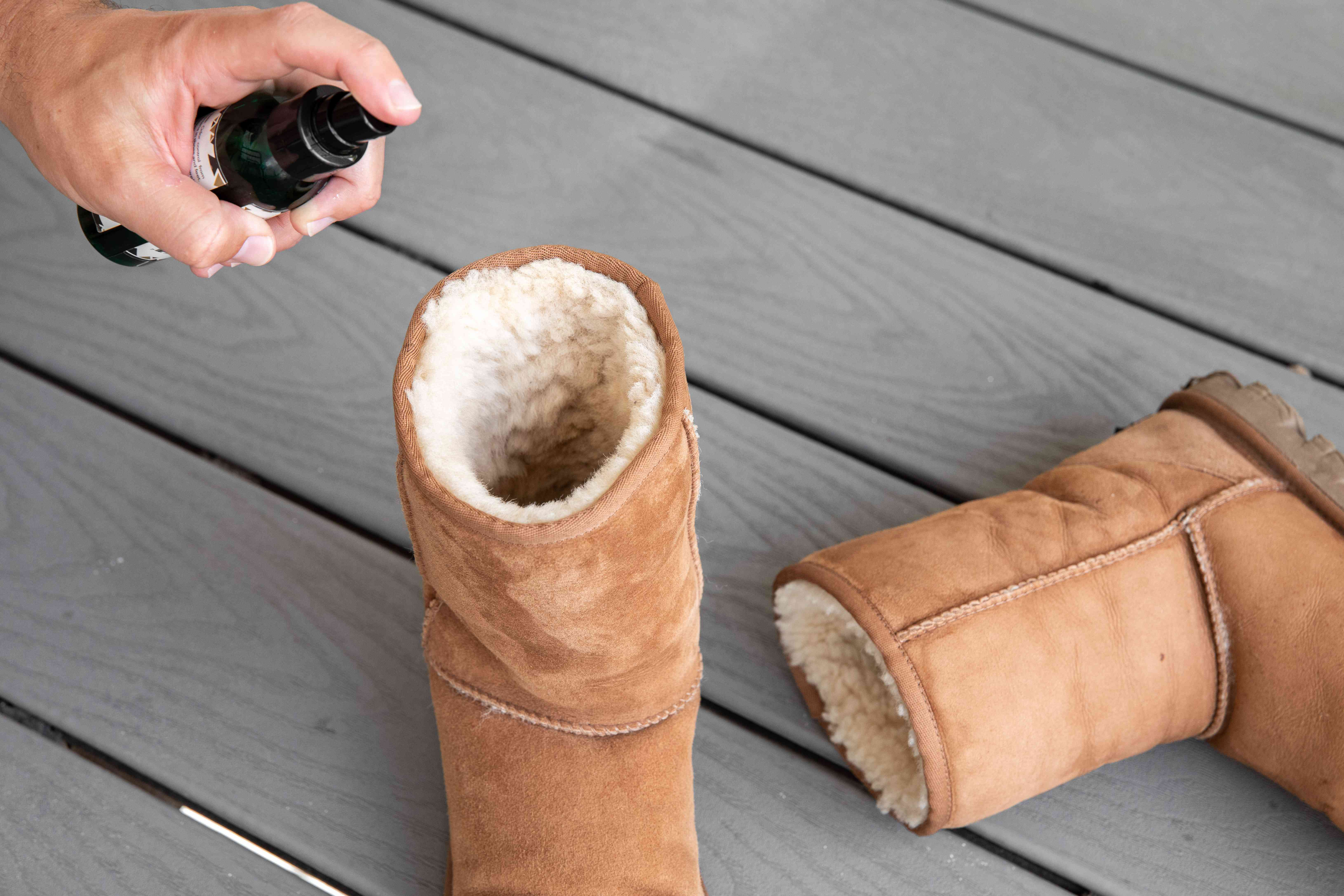 Someone using fungal spray inside an Ugg boot