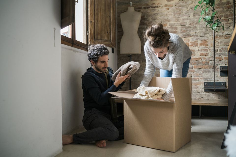 Young couple packing cardboard box on a floor