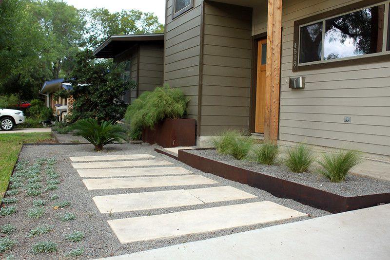 Large white pavers set in grey gravel walkway next to modern exterior house design