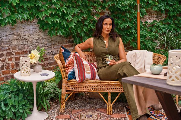 Padma poses on a rattan settee among some of the entertaining items she curated for Etsy