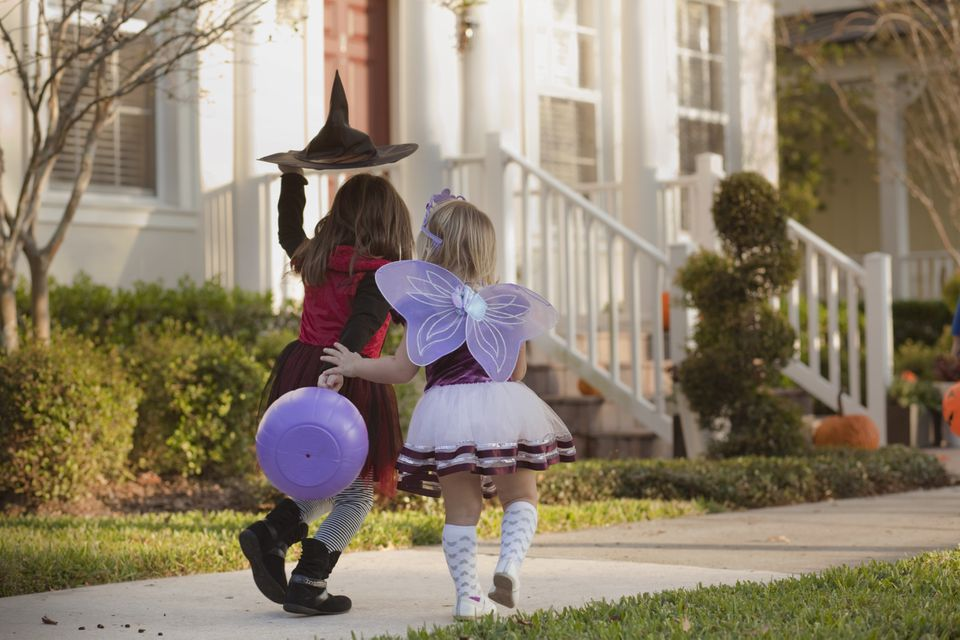 two trick-or-treaters on a sidewalk in costume