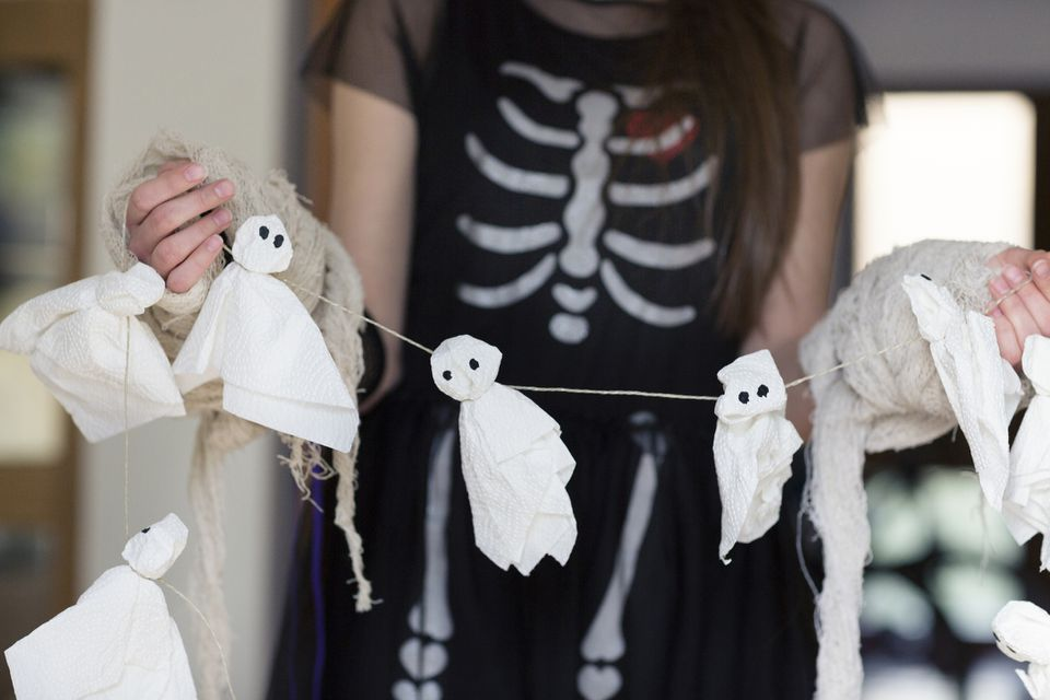 Teenager holding tissue paper Halloween ghost decoration