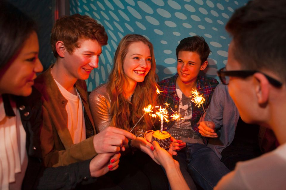 Group of teenagers sitting around birthday cake with sparklers
