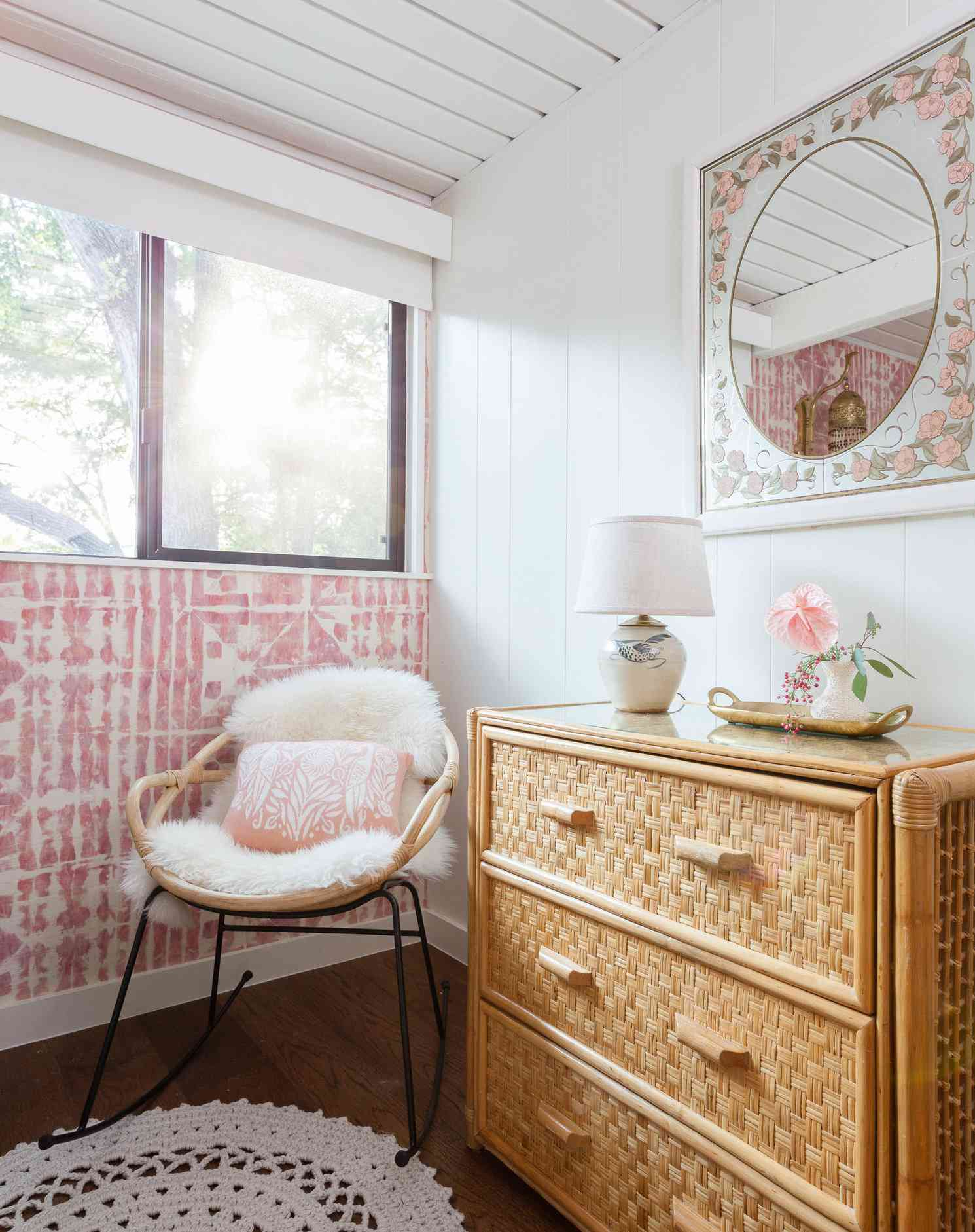 pink bedroom with mirror hanging above dresser