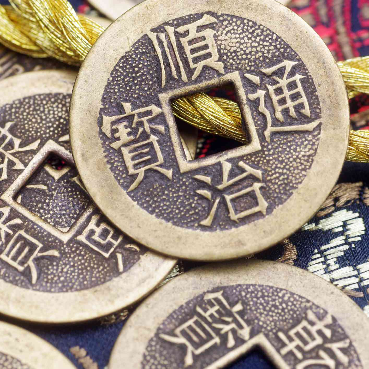 Ancient Chinese copper coins on an embroidered brocade background. Golden embroidered cord in background.