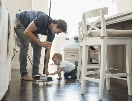 man and baby cleaning floor