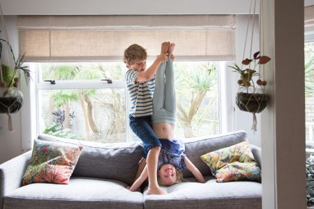 Siblings Brother Helping And Supporting Sister To Do A Headstand
