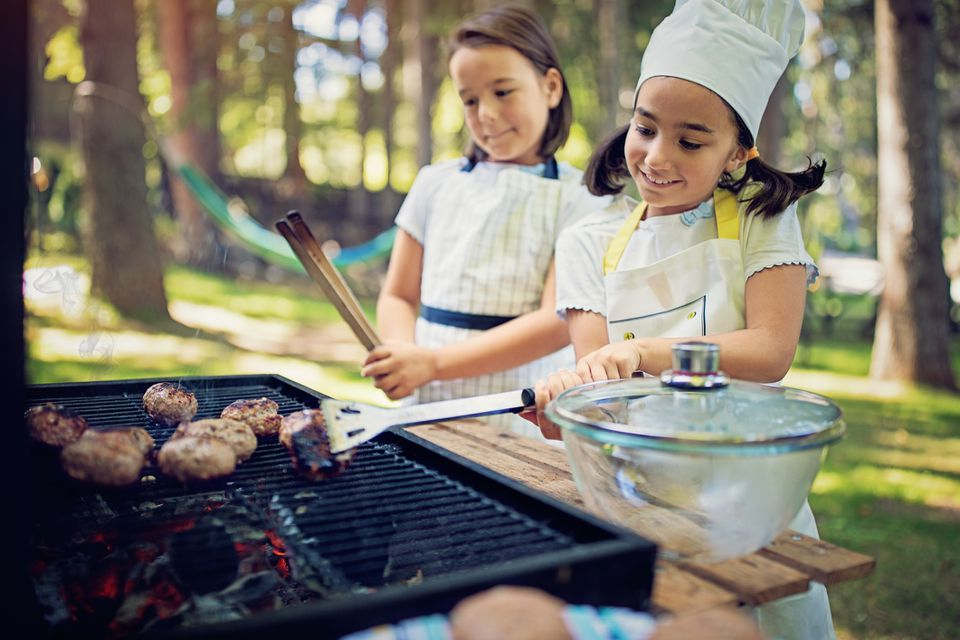 Little girls are doing barbecue in the back yard
