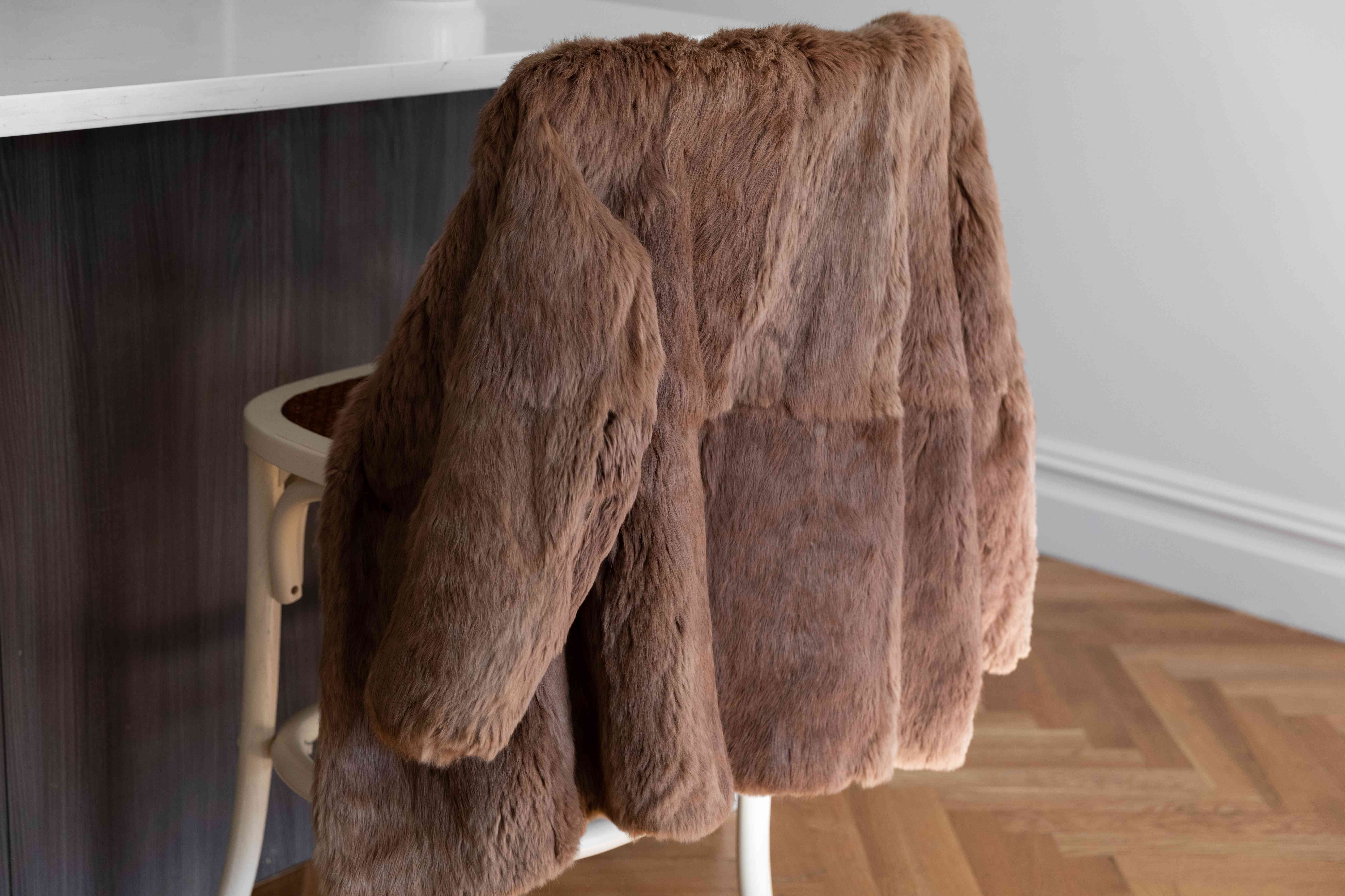 A brown fur coat hanging on a chair back