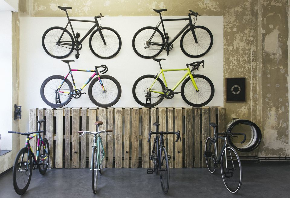 Road bikes hanging on a wall and parked on the floor