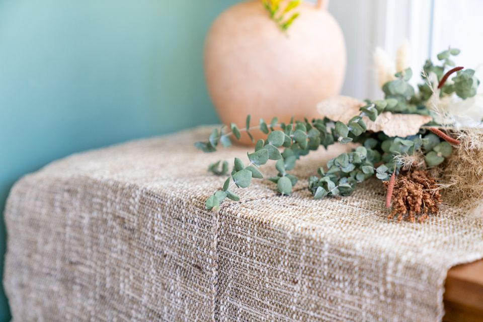 Burlap fabric decorating surface with eucalyptus and fried florals on top