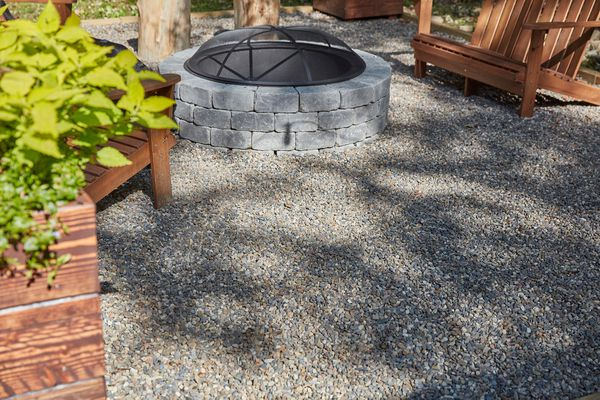 Pea gravel surrounding circular gray-stoned fire pit with wooden furniture and plants nearby