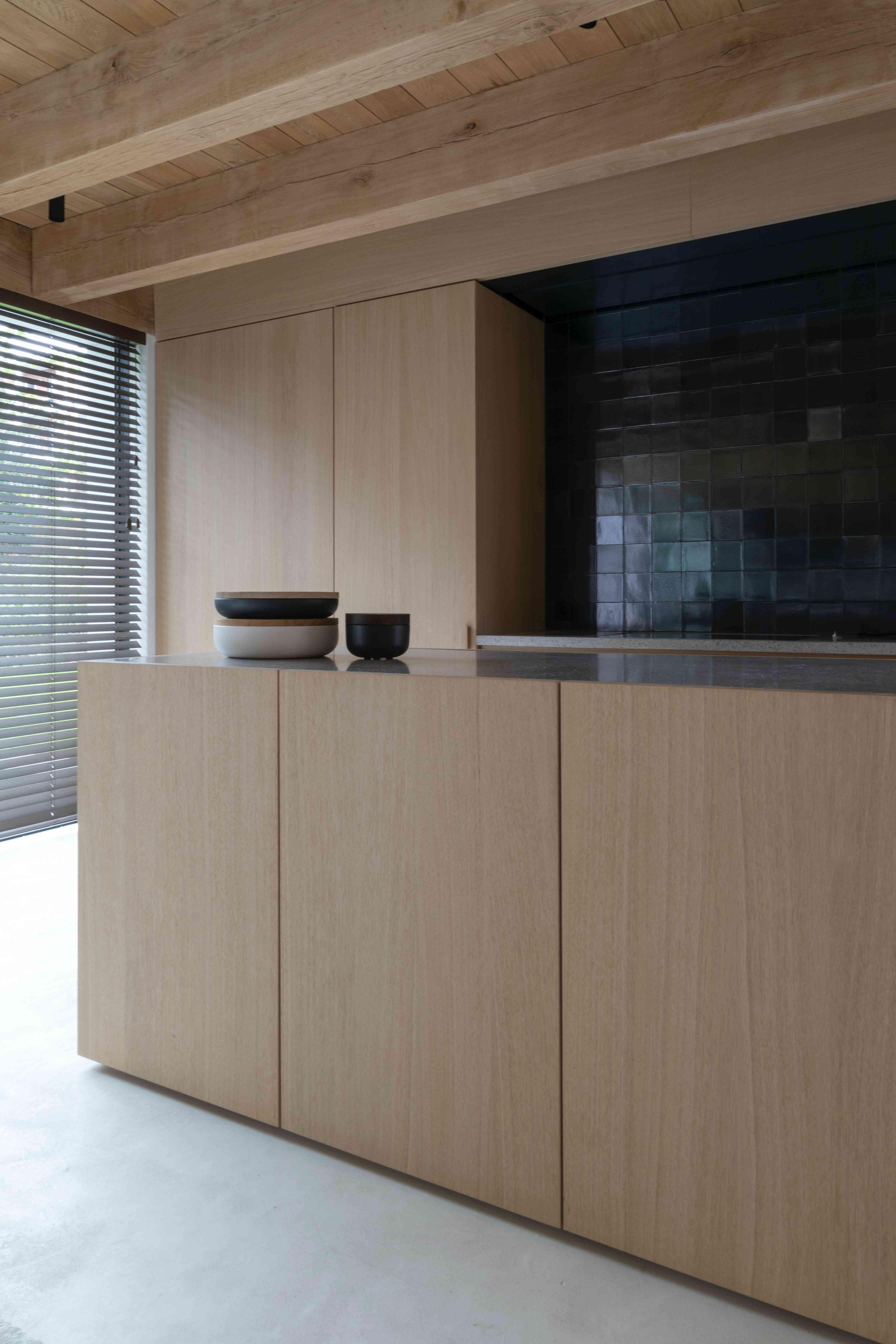 wood kitchen with black backsplash