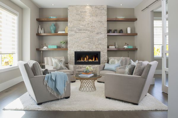 Beige living room with four chairs, table, lit fireplace, and shelving.