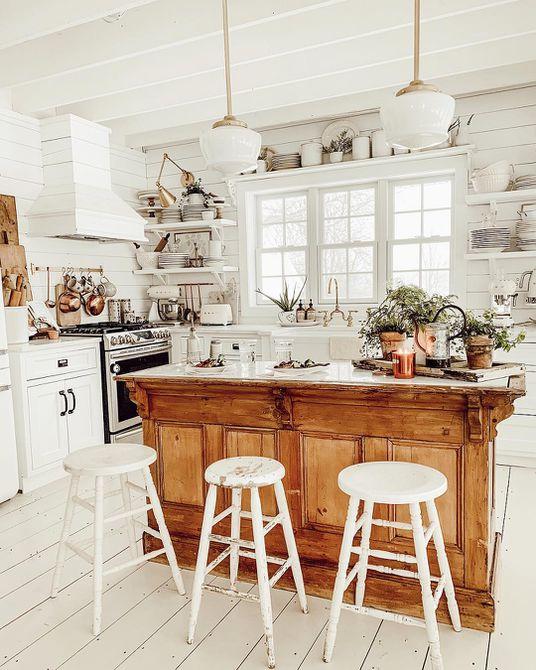 Cocina blanca con una isla de cocina de madera