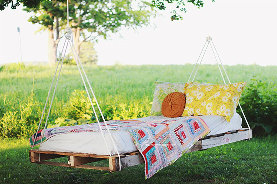 A bed made of pallets hanging from a tree