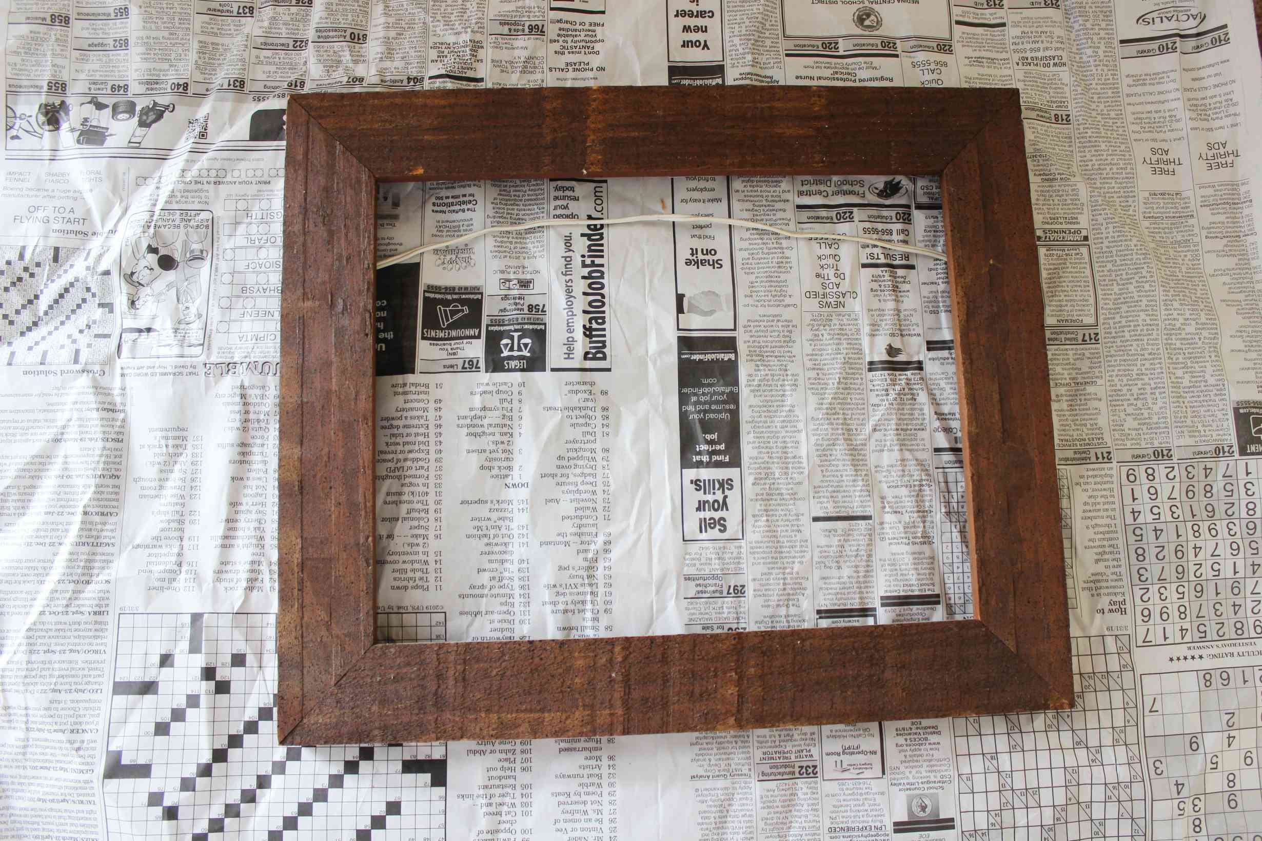empty wood picture frame on newspaper