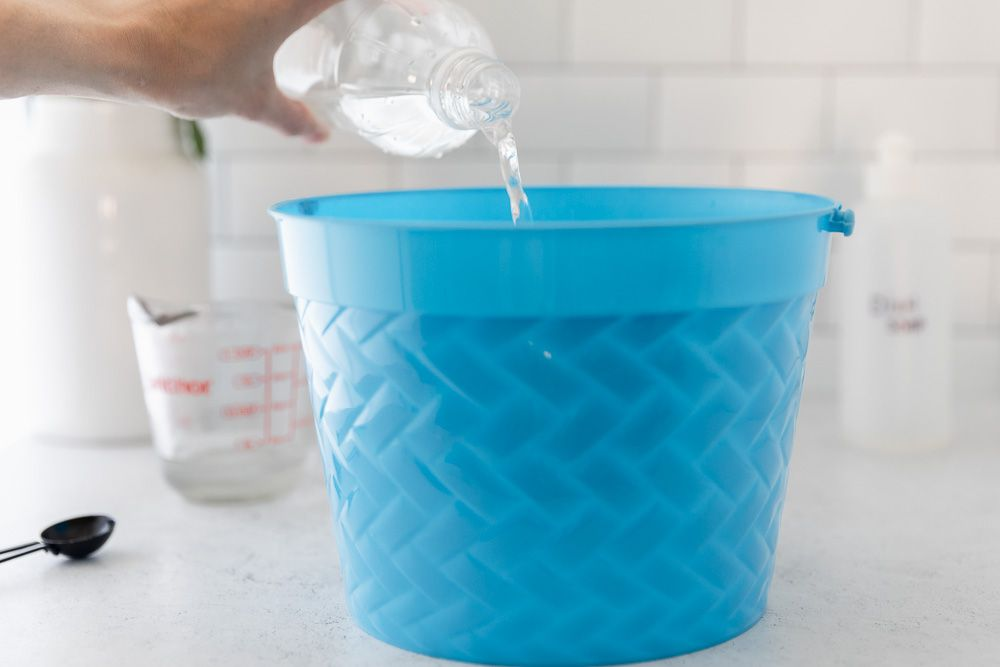 Distilled white vinegar poured into blue bucket with water for cleaning solution