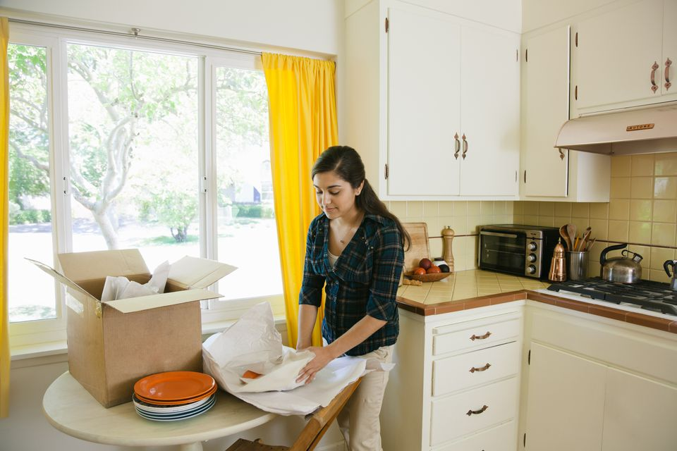 woman packing dishes in kitchen
