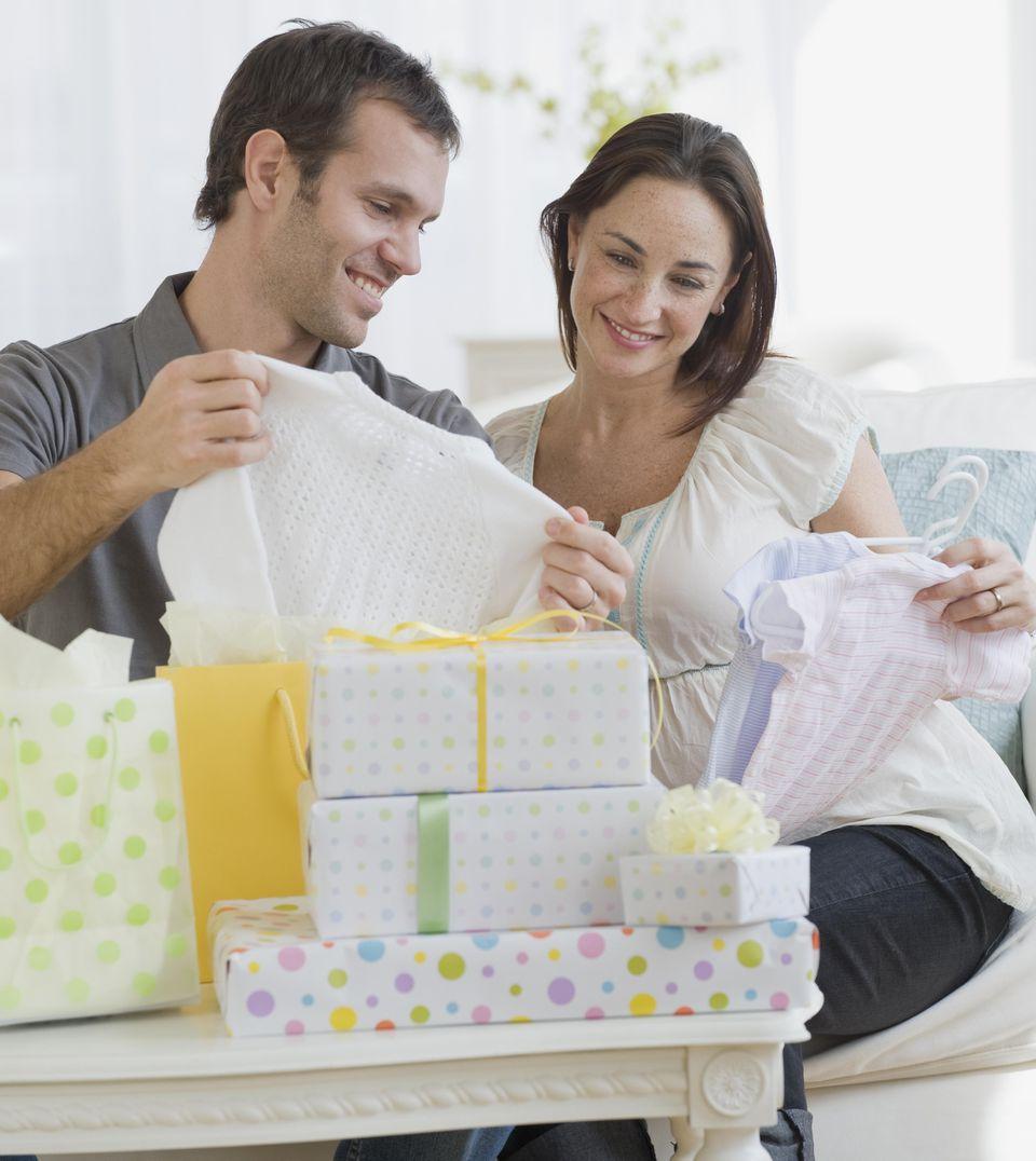 Pregnant Hispanic couple opening gifts
