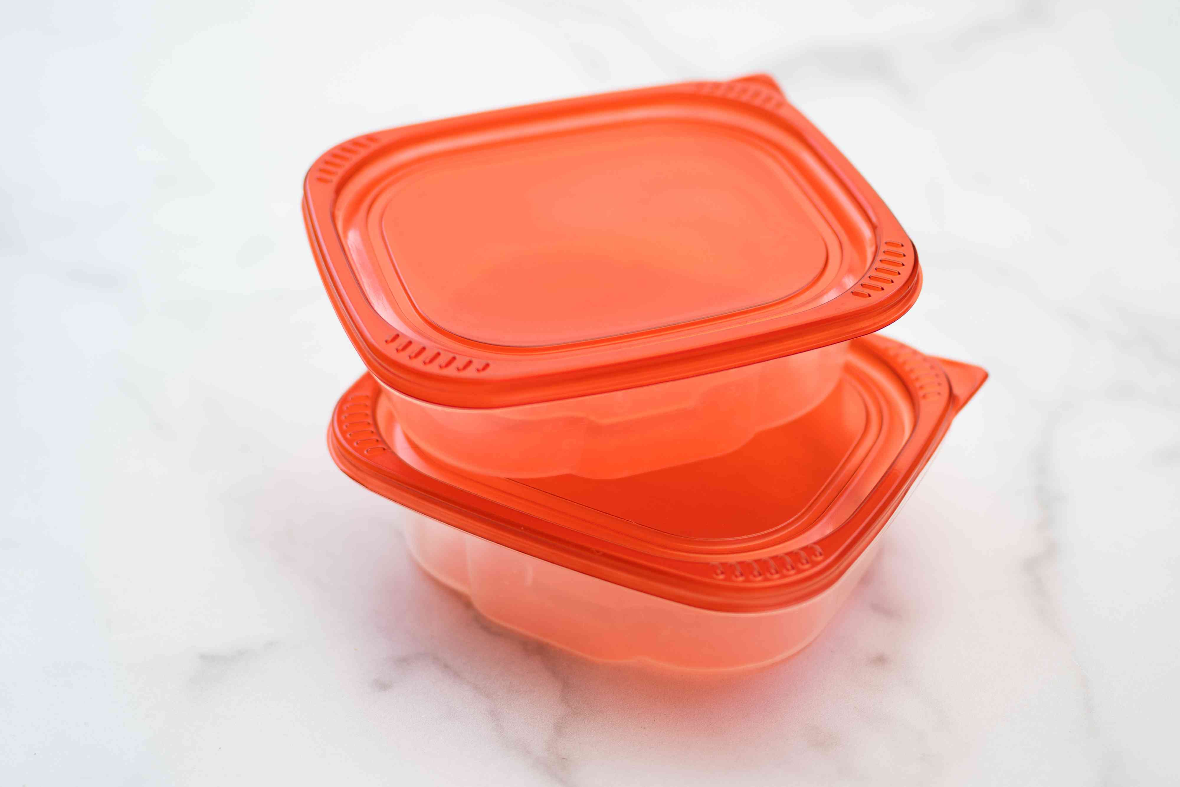 Thin plastic containers with red lids not placed in dishwasher