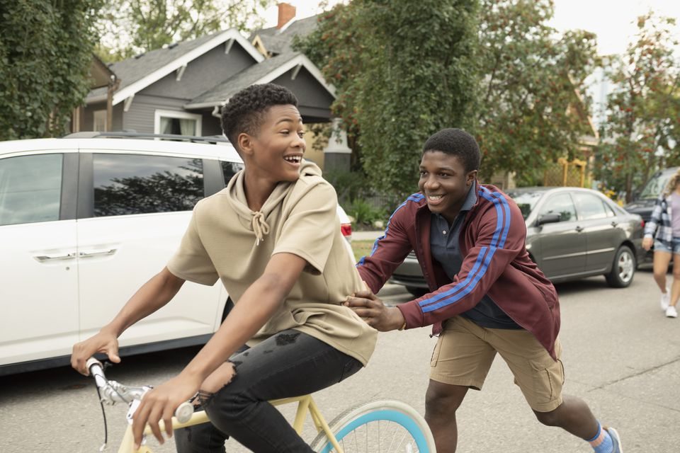 Playful teenage boy pushing friend on bicycle on street