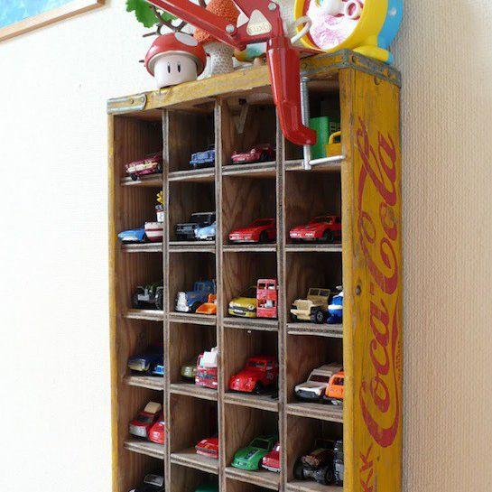Vintage bottle crate repurposed as toy car storage shelf