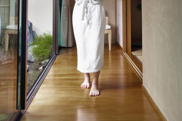 A woman with tea walking across a bamboo floor