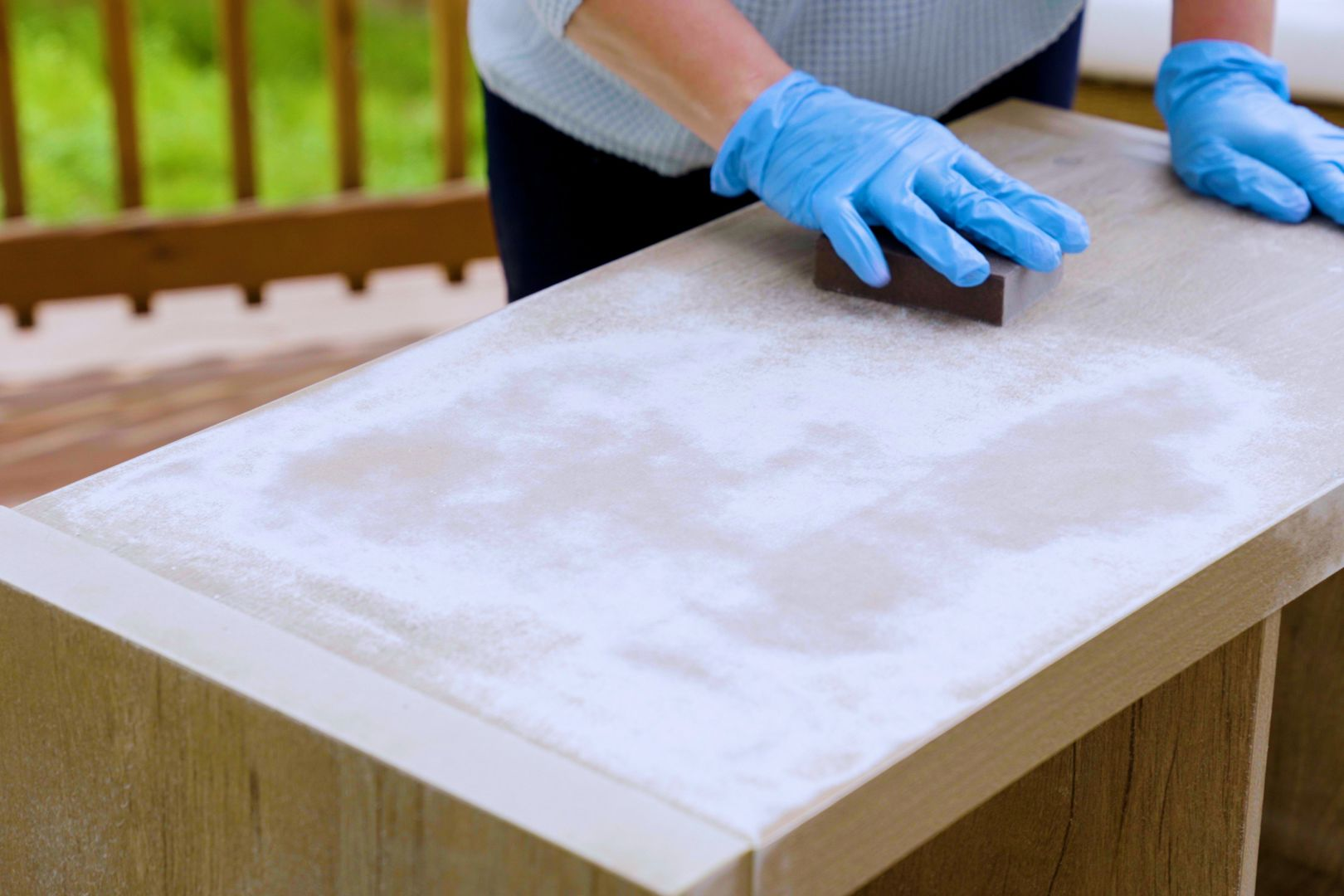 Particleboard furniture sanded down by hand with blue gloves for refurbishing