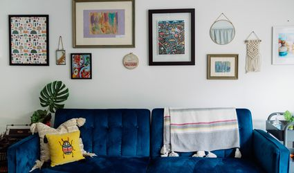 Blue velvet couch in a living room with a gallery wall behind.