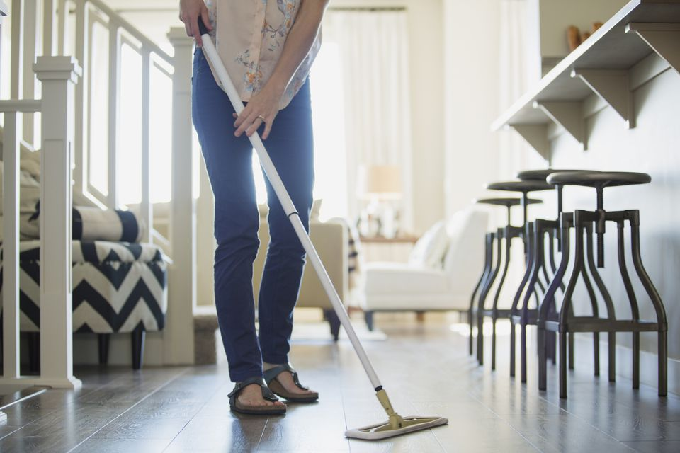 Mid-adult woman dusting floors in modern home.