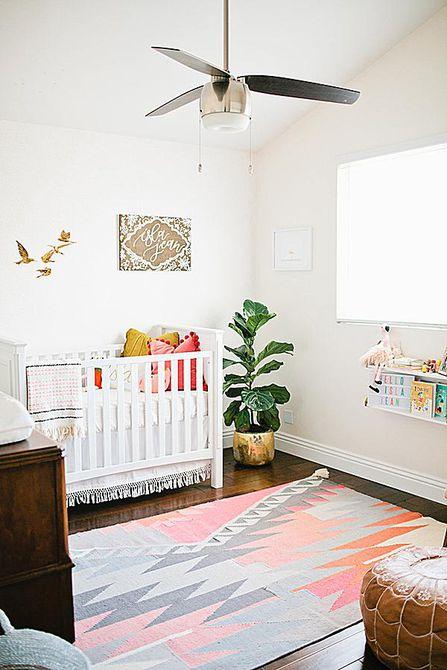 Habitación infantil simple, blanca con una decoración mínima y un ventilador de techo