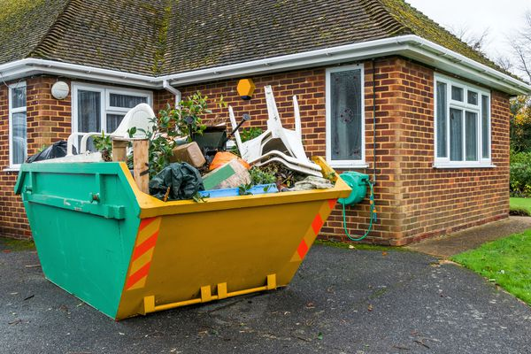 Construction dumpster in the driveway of a home