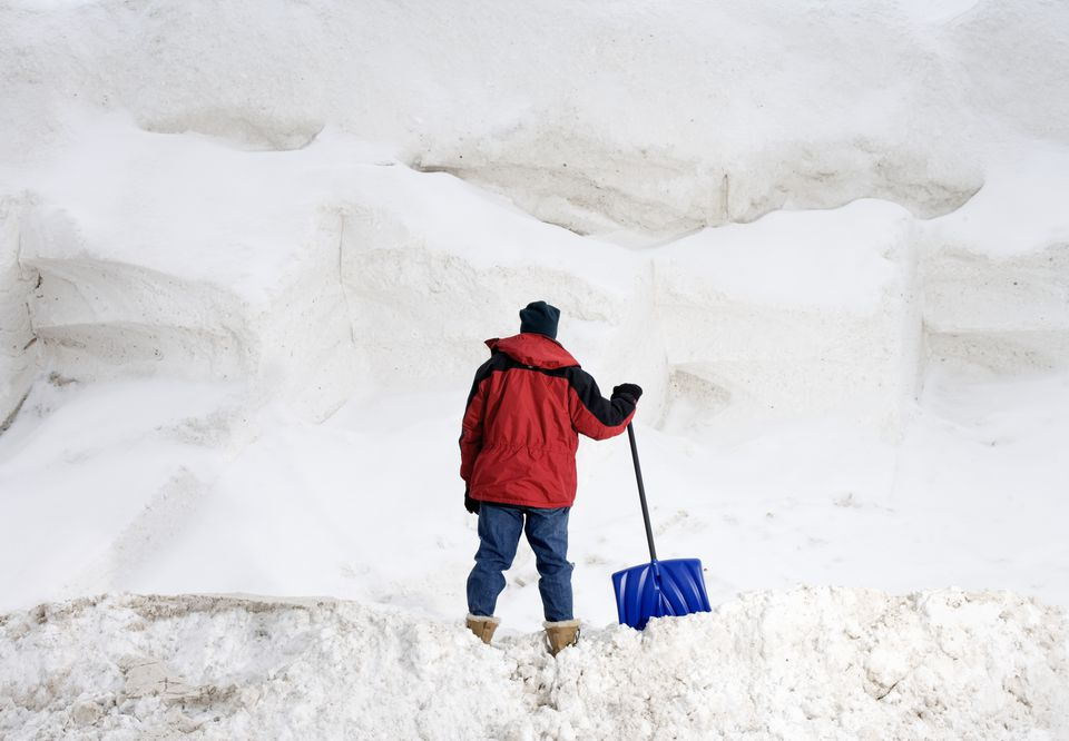 Man with shovel staring at big pile of snow