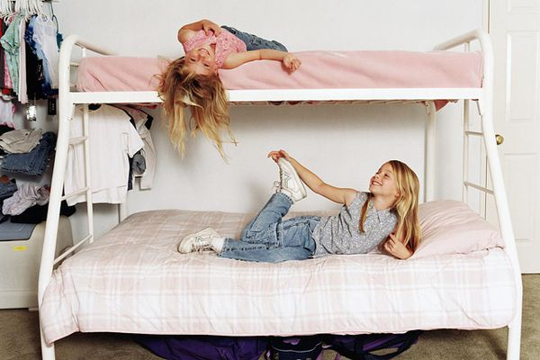Twin sisters smiling and lying on bunk beds.