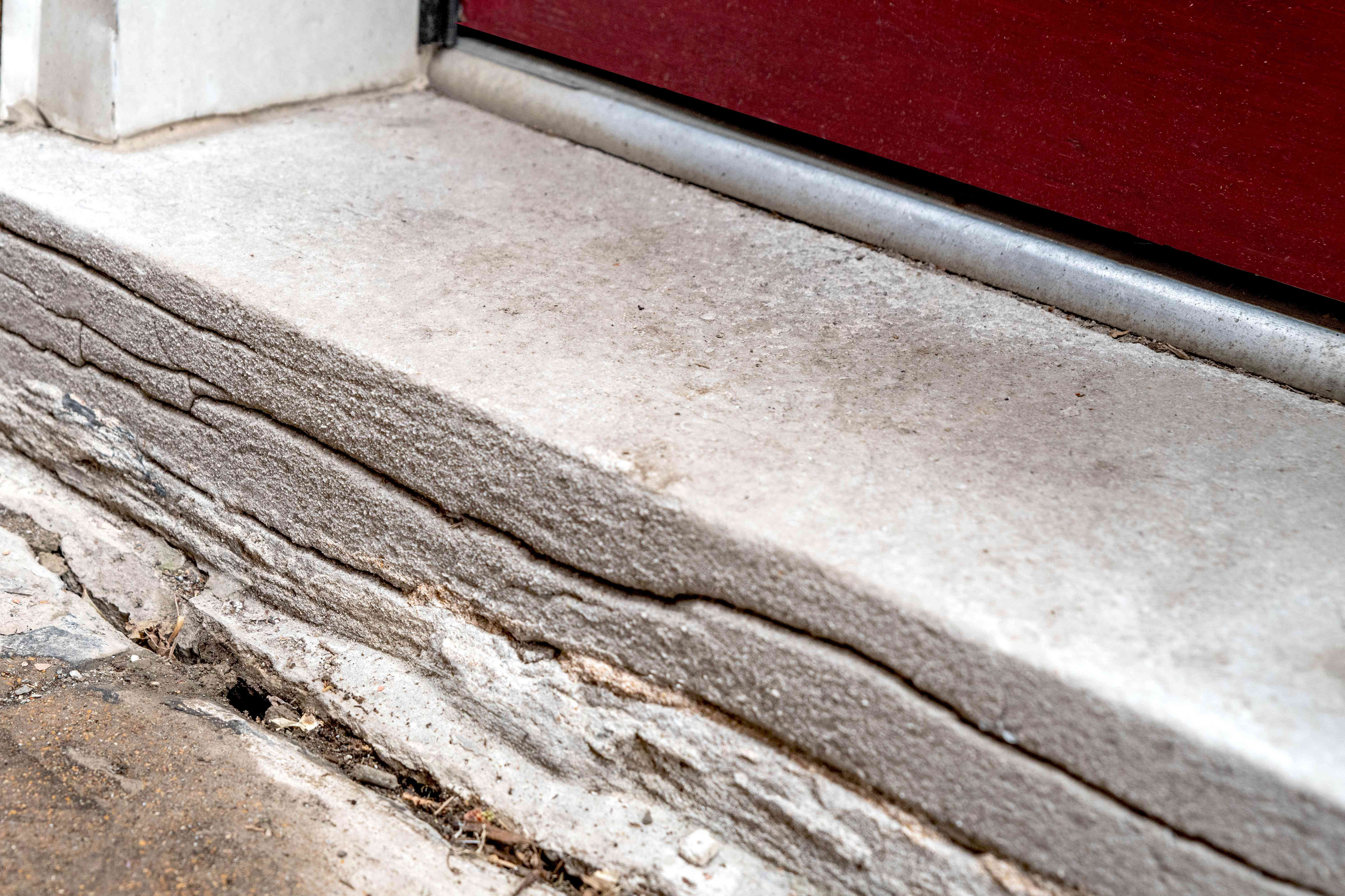 Doorway step with cracks in front